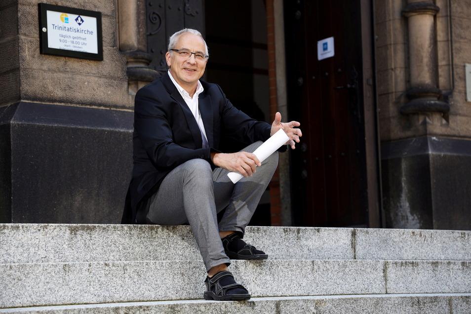 Pfarrer Johannes Grasemann sitzt auf den Stufen vor der Trinitatis-Kirche. Hier hält er am Sonntag seinen Abschiedsgottesdienst.