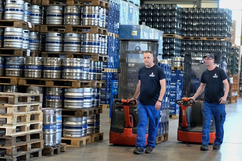 Zwei Mitarbeiter der Privatbrauerei Meißner Schwerter transportieren im Lager Bierkästen an Fässern vorbei. Letztere werden auf unbestimmte Zeit nicht gebraucht.