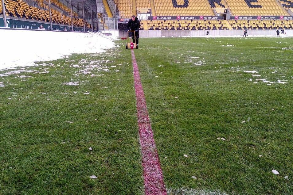 Helfer haben den Rasen im Dresdner Rudolf-Harbig-Stadion vom Schnee beräumt, jetzt werden mit roter Farbe die Linien gezogen.