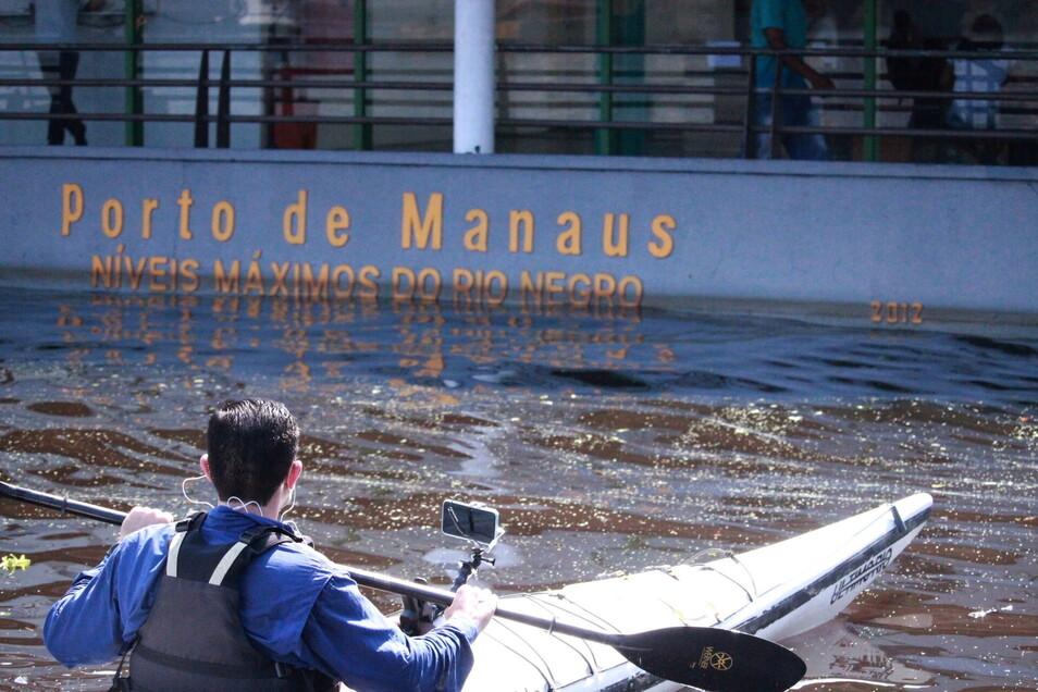 Ein Mann paddelt mit seinem Kayak im Hafen von Manaus.