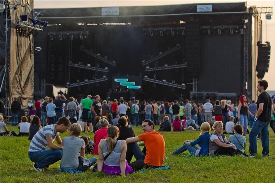Die Besucher entspannen in der Dämmerung vor der Bühne.