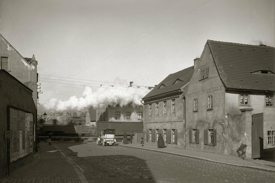 Dresden-Plauen, Dorfstraße, 1911. Fotos von Außenbezirken sind im 19. Jahrhundert eher selten. Umso kostbarer diese Momentaufnahme: Der Fortschritt bricht gewaltig herein - in Gestalt der Dampfwolke eines durchrauschenden Zuges.