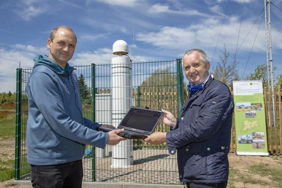 Frank Strugale (li) vom Landesvermessungsamt und Thomas Schmidt, Sachsens Minister für Regionalentwicklung, nahmen in Zinnwald die Sapos-Bodenstation in Betrieb.