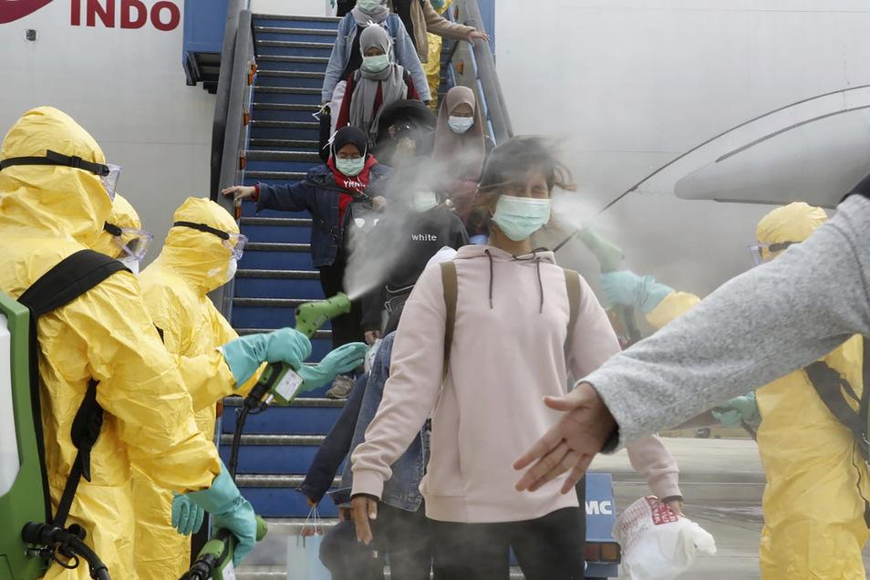 Indonesische Staatsbürger, ausgeflogen aus Wuhan, werden bei ihrer Ankunft auf dem Flughafen Hang Nadim mit einem Antiseptikum besprüht. Sie wurden in eine Quarantänezone auf einer abgelegenen Insel am Rande des Südchinesischen Meeres transportiert.