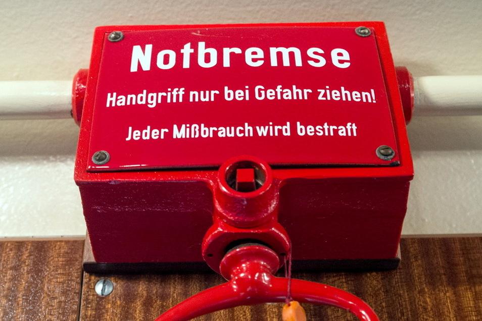 Eine Notbremse in einer historischen S-Bahn. Die Corona-Notbremse mit verbindlichen Regeln für den Kampf gegen die dritte Welle der Pandemie in ganz Deutschland führt zu heftigen Diskussionen.