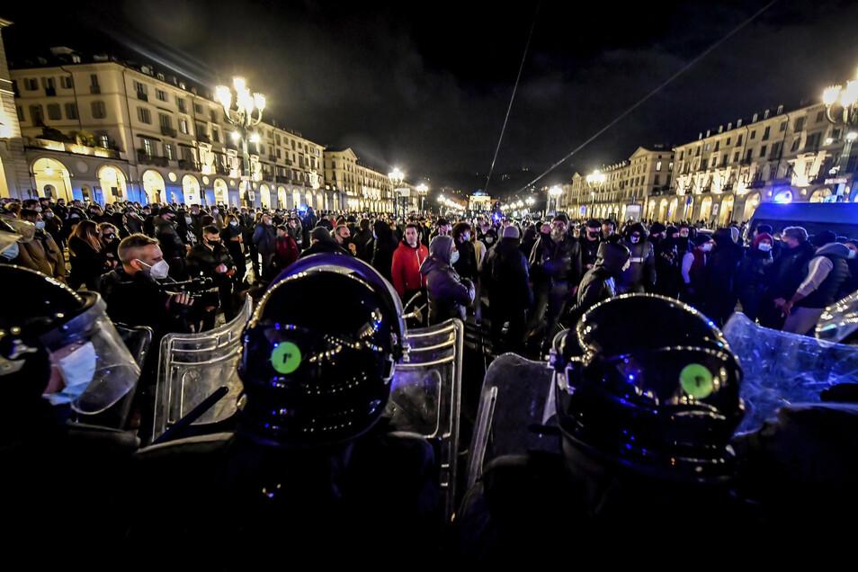 Italien, Turin: Menschen protestieren am Montagabend gegen die Restriktionsmaßnahmen der Regierung zur Eindämmung der Verbreitung von COVID-19.