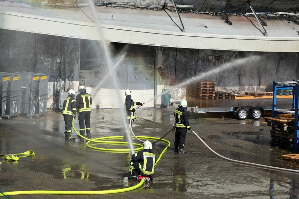 Mit mehrere Löschschläuchen versuchen die Feuerwehrleute die Lagerhalle in Großschirma zu löschen.