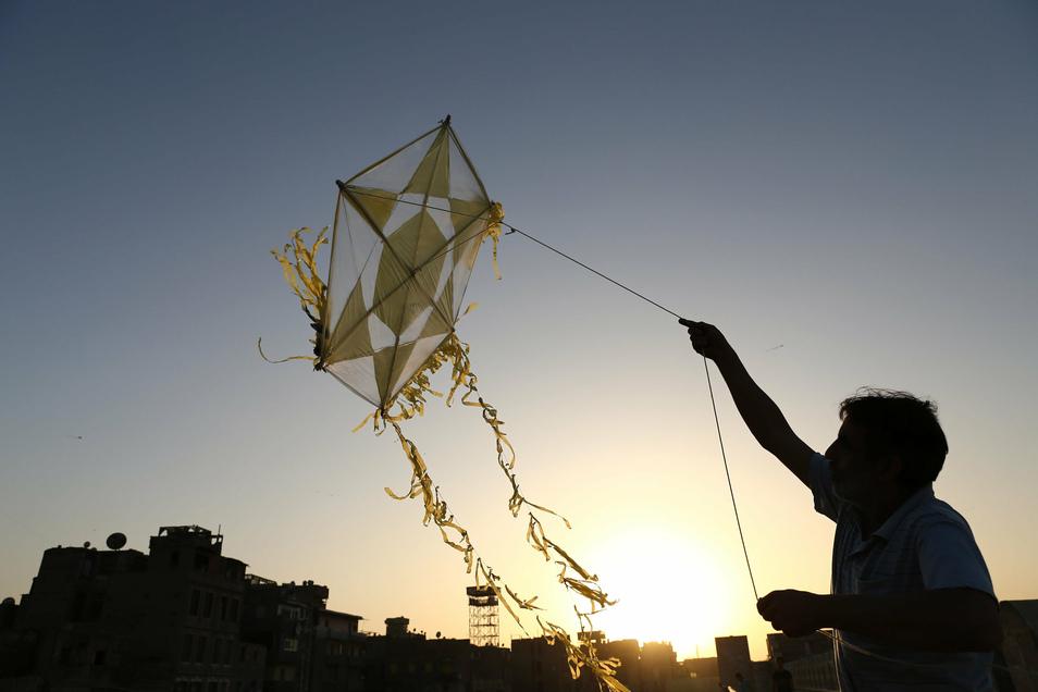 Ein Mann lässt auf dem Dach eines Gebäudes in Kairo einen Drachen steigen.