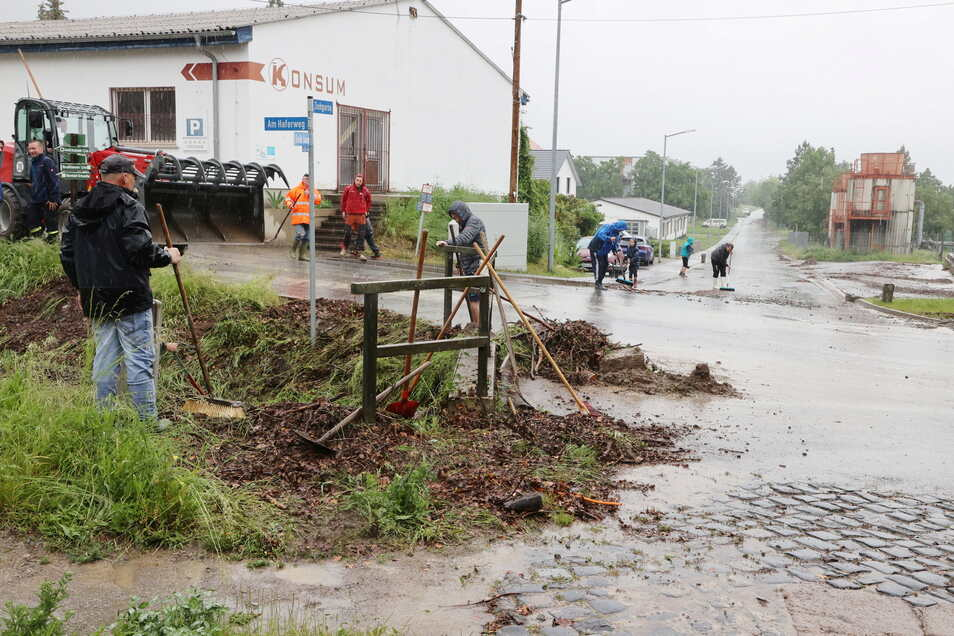 Helfer beseitigen Unrat aus einem Dorfbach nach heftigen Regenfällen in Gierstädt am Sonntagmorgen.