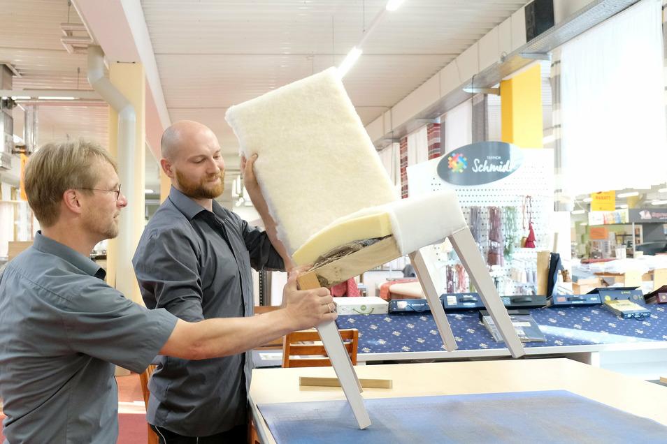 Polsterer Erik Zschoge (M.) richtet eine Schauwerkstatt im Geschäft von Holger Schmidt (l.) Teppich Schmidt an der Berghausstraße ein.