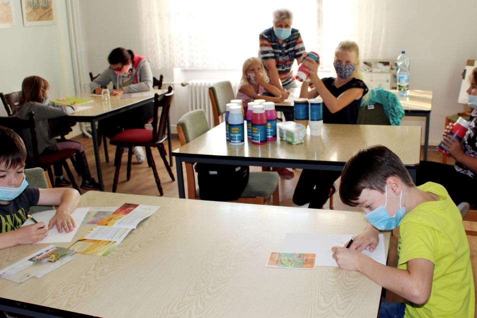 Am vorderen Tisch arbeiten Nico und Nils an Motiven für die im Text geschilderte Litfaßsäule. Dahinter schütteln Romy und Sophie ordentlich die Farben, die lange ungenutzt auf bessere (Mal-) Zeiten hatten warten müssen. Trotz Mundschutz und Sicherhei