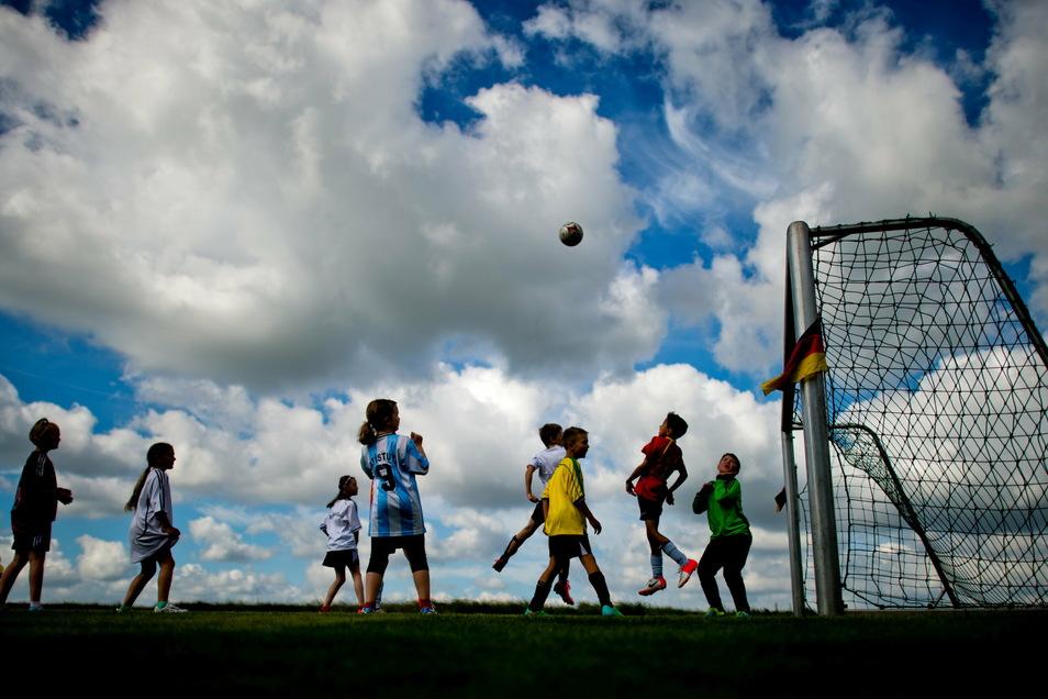 Kinder spielen auf dem Testgelände des Bundessortenamt - Prüfstelle Scharnhorst Fußball. Die Rückkehr zum Vereinssport ist ein großes Anliegen von Initiativen und Verbänden.