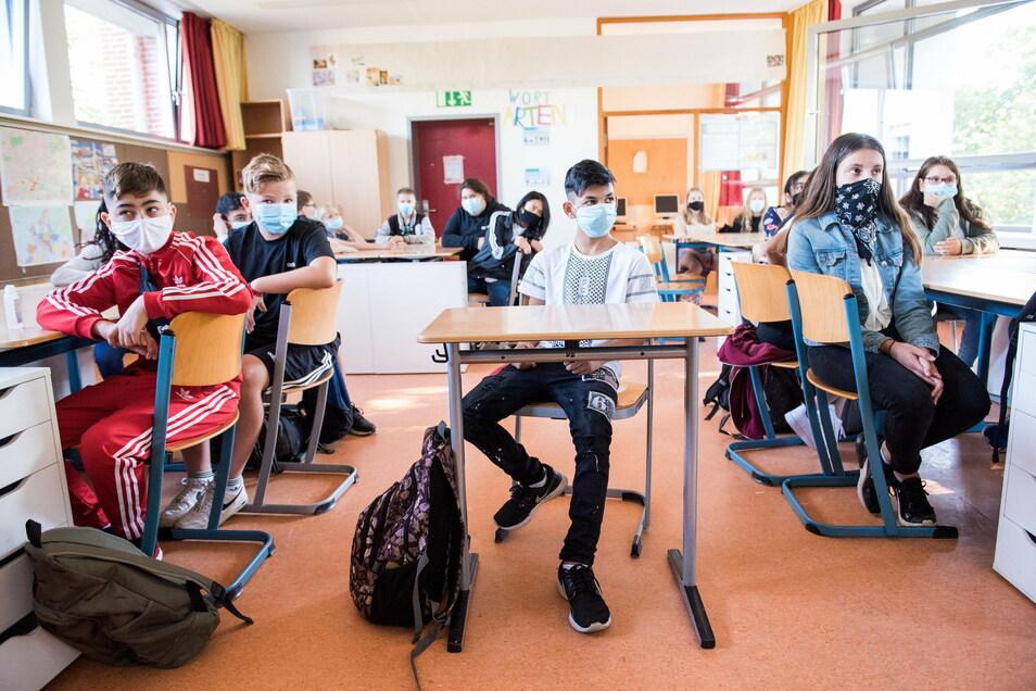 Schüler einer 7. Klasse sitzen zu Beginn des Unterrichts mit Mund-Nasen-Bedeckungen im Klassenraum. Auch im Landkreis Meißen steigen die Corona-Fälle in Schulen und Horten. Viele Schüler und Lehrer sind auch von Quarantäne betroffen.