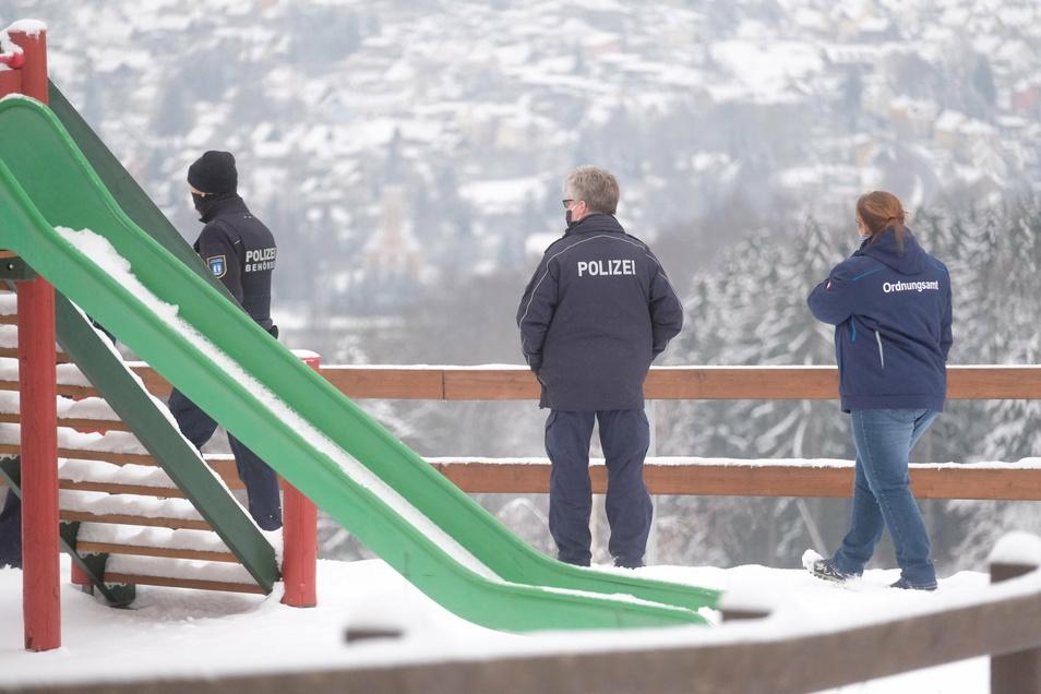 Mitarbeiter von Polizei und Ordnungsamt stehen an einem Rodelhang in Augustusburg.