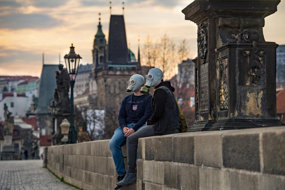 Ein Paar mit Gasmasken sitzt auf der Karlsbrücke in Prag. Auch Tschechien lockert einige Bestimmungen.