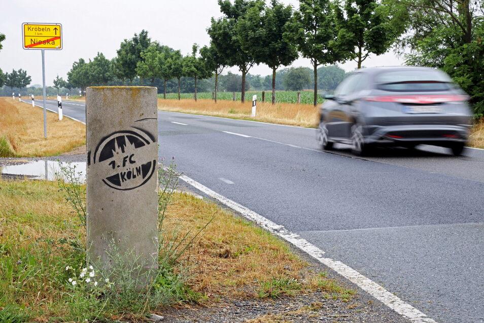 Der preußisch-sächsische Grenzstein bei Nieska ist von Kölner Fußballfans beschmiert worden. Deutlich zu sehen ist, dass das Ortseingangsschild weit hinter dem Grenzstein steht. Aber wie kommt es dahin?