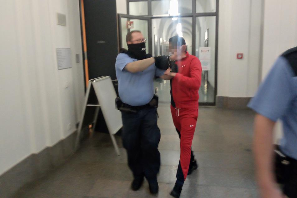Der Angeklagte verbirgt auf dem Weg in der Gerichtssaal sein Gesicht. Ihm und seiner Frau wird Drogenhandel in 61 Fällen vorgeworfen.
