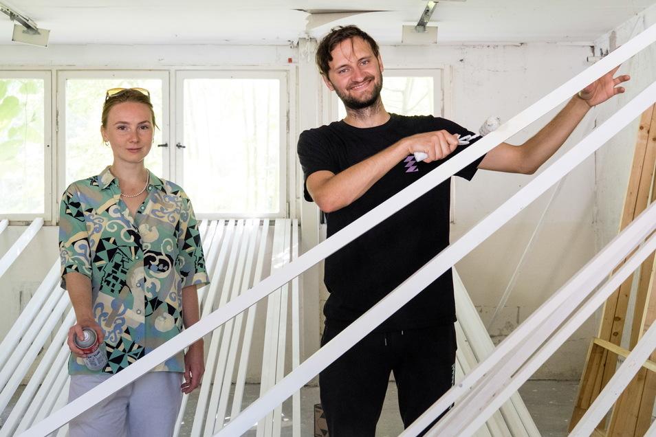 Kira Schmieg und Felix Schuster vom Festivalteam bereiten ein Kunstwerk für die Zukunftsvisionen-Ausstellung vor.