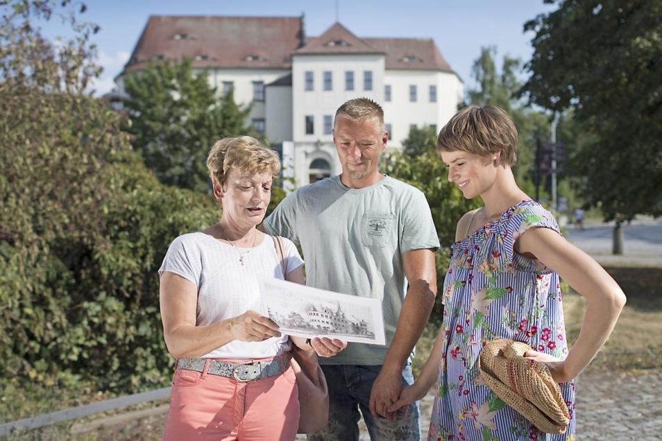 Das Bild zeigt eine Gästeführerin mit Besuchern vor dem Schloss in Hoyerswerda.