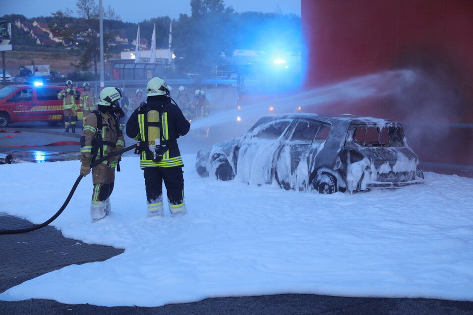 Die Feuerwehr löschte Auto und Fassade des Supermarktes mit Schaum und Wasser.