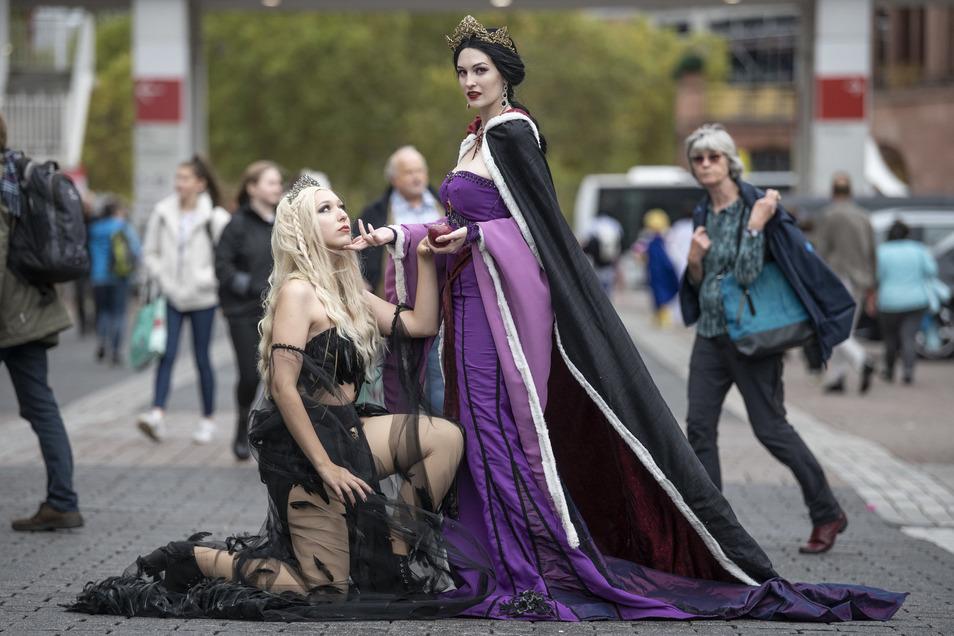 """Inmitten der Buchmesse-Besucher posieren zwei als """"Böse Königin"""" (r) und """"Rabe"""" kostümierte Cosplayerinnen auf dem Messegelände."""