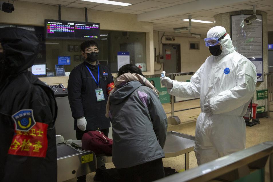 Ein Mitarbeiter trägt einen Sicherheitsanzug und überprüft einen Fahrgast in einer U-Bahn-Station mit einem digitalen Thermometer.