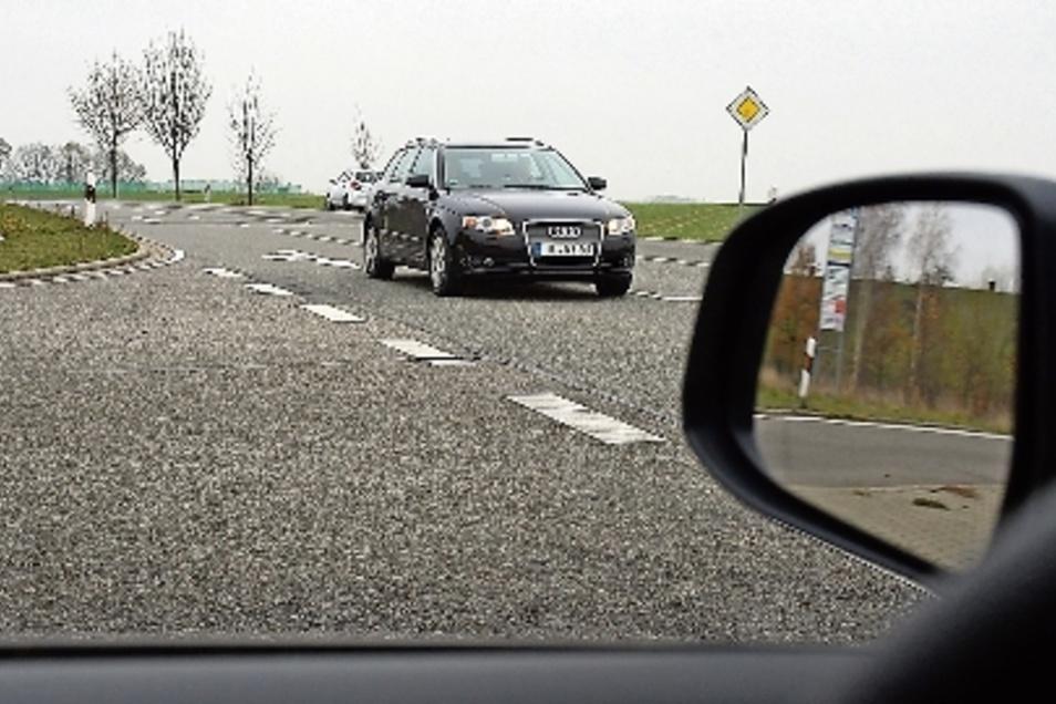 Blick aus Richtung Hartha nach links: Die Straße selbst ist bis in Höhe der großen Hinweistafel erkennbar, dennoch sieht man Autos auch aus weiterer Entfernung.