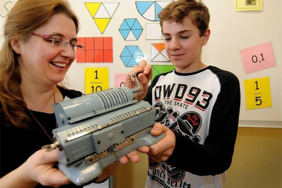 Mathematiklehrerin Kerstin Schmiedchen und Luke Beyrich aus der siebten Klasse probieren an der Oberschule Roßwein eine historische, russische Rechenmaschine aus. In der siebten Klasse wird die Geschichte der Rechenmaschinen und Hilfsmittel nachempfunden und teilweise nachgebaut.
