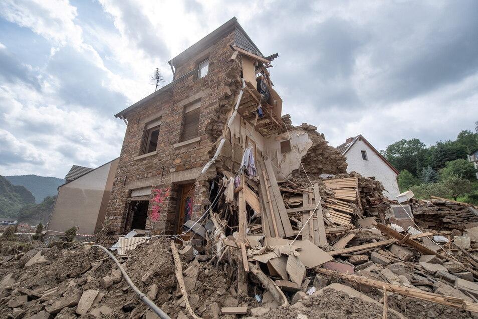 Ein völlig zerstörtes Haus am Ortseingang von Altenahr. Helfer sind Tag und Nacht damit beschäftigt die Straßen in den weitgehend zerstörten Orten wieder befahrbar zu machen.