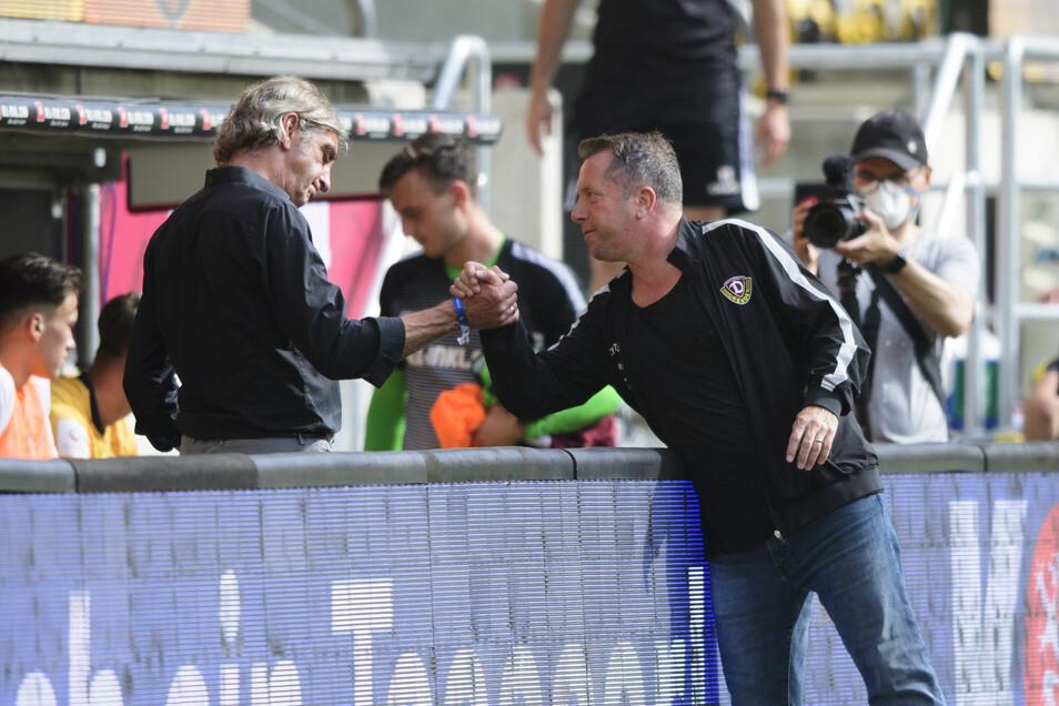 Dynamos scheidender Sportdirektor Ralf Minge klatscht nach dem Spiel mit Trainer Markus Kauczinski ab.