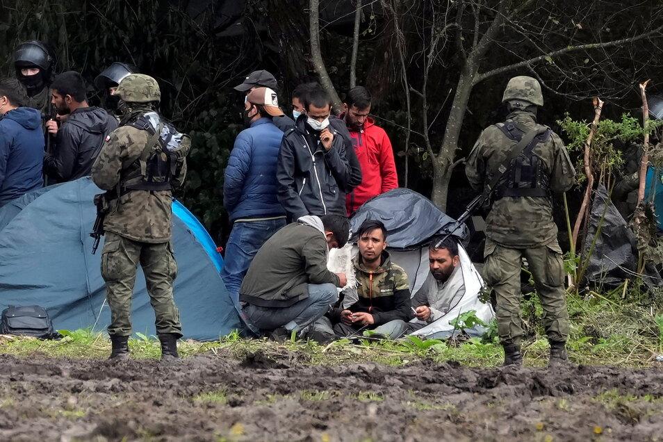Polnische Sicherheitskräfte umringen Migranten, die an der Grenze zu Weißrussland festsitzen.