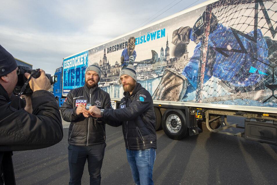 Die Spieler Florian Proske (re.) und Steven Rupprich posieren auf dem Gelände des Logistik-Unternehmens Dachser in Radeburg vor einem neuen Truck, der auf seiner Außenfläche für die Dresdner Eislöwen wirbt.