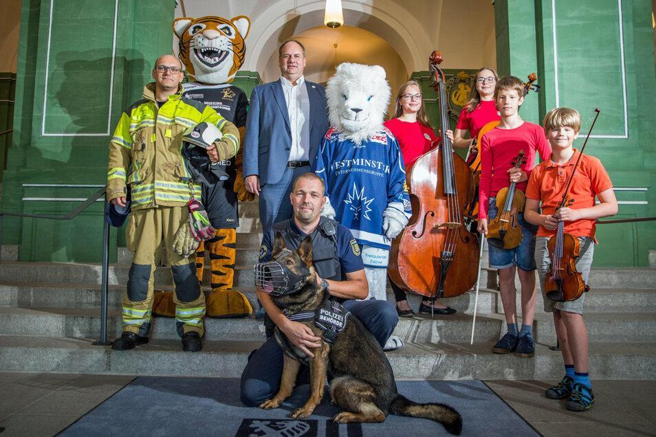 Der OB posiert mit Maskottchen und jungen Musikern.