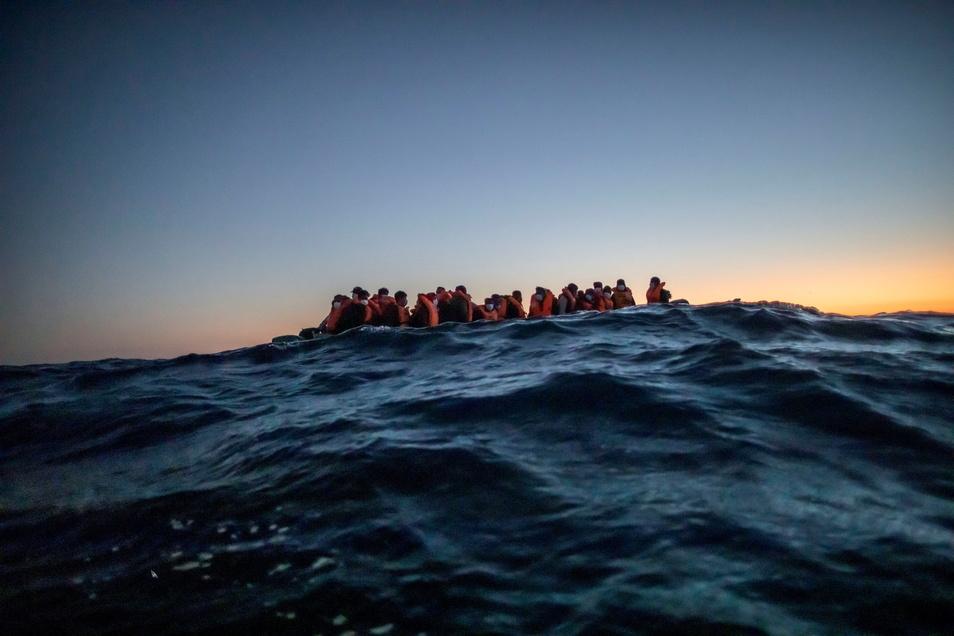 Migranten aus verschiedenen afrikanischen Nationen warten in einem Boot auf Helfer der spanischen NGO Open Arms, die sich ihnen 122 Meilen vor der libyschen Küste im Mittelmeer nähern.