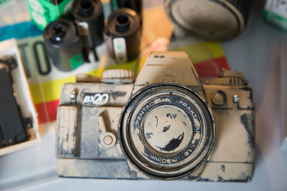 Für die Spiegelreflexkamera Praktica BX 20 schrieb Ute Grohmann als junge Ingenieurin die Bedienungsanleitung. Die Flut 2002 hinterließ Schlamm auf allen Kameras und technischen Geräten in der Werkstatt ihres Vaters. Zum Andenken steht dieser Fotoapparat