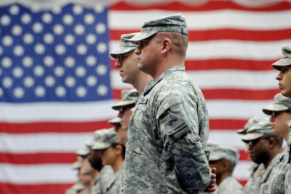 US-Soldaten stehen nach ihrer Ankunft auf der US-Airbase in Wiesbaden-Erbenheim vor einer US-Flagge. Mit 35 000 US-Soldaten gilt Deutschland als wichtigster Stützpunkt der USA in Europa.