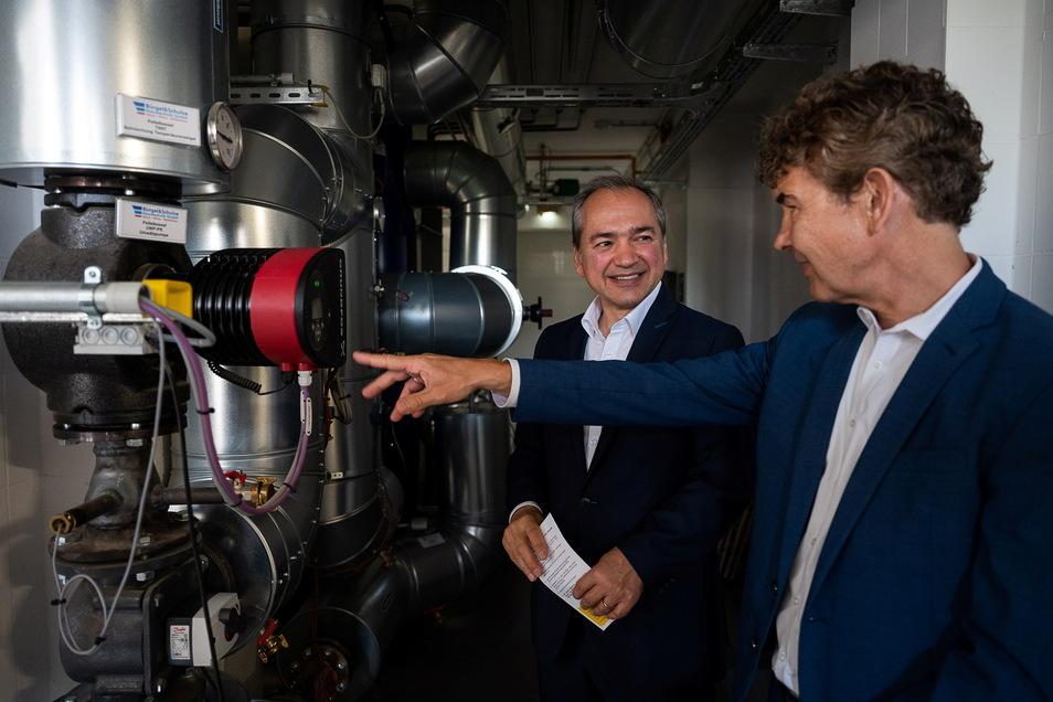 OB Octavian Ursu (l.) und Stadtwerke-Chef Matthias Block schauen sich die neue Energiezentrale EEQ1+ im Keller der Görlitzer Waldorfschule an.
