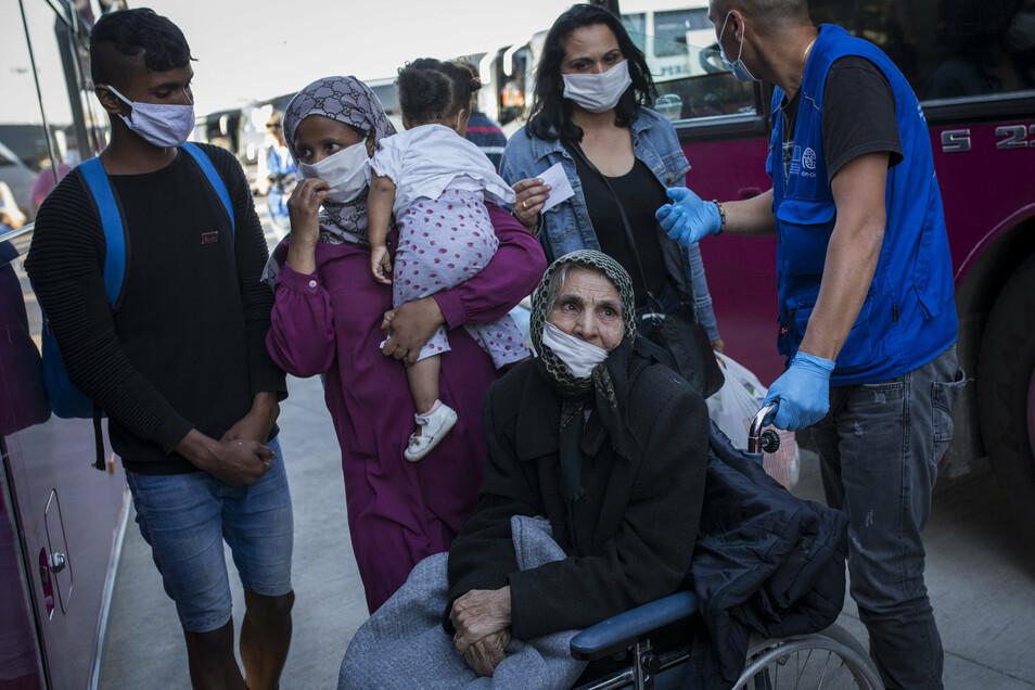 Flüchtlinge aus Moria und von anderen griechischen Inseln stehen im Hafen von Lavrio bei Athen. Griechische Behörden verlegten etwa 1.000 Migranten, zumeist Familien und anerkannte Flüchtlinge, auf das Festland.