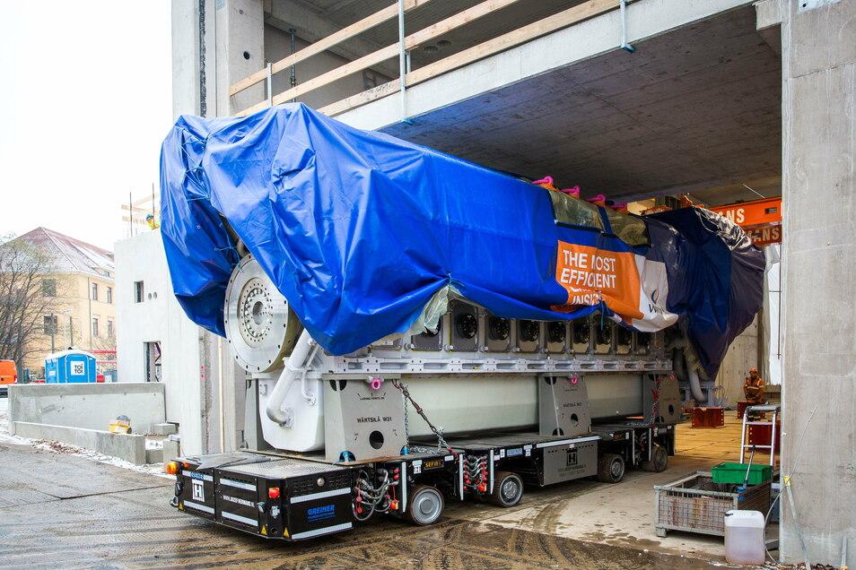 100 Tonnen Last auf Fahrt. Auf einem ferngesteuerten Wagen wird der Motor an seinen Platz bugsiert.