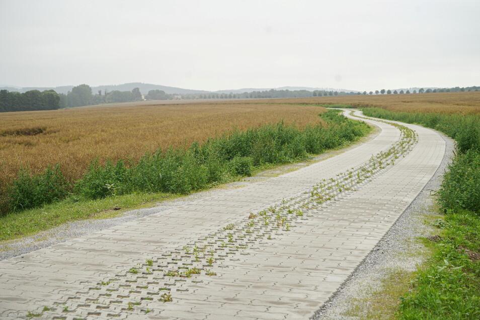 Für rund 700.000 Euro wurde der Siedlungsweg auf einer Länge von etwa 1.700 Metern mit Betonpflaster ausgebaut. Der Maßnahme voraus ging ein umfangreiches Flurneuordnungsverfahren.