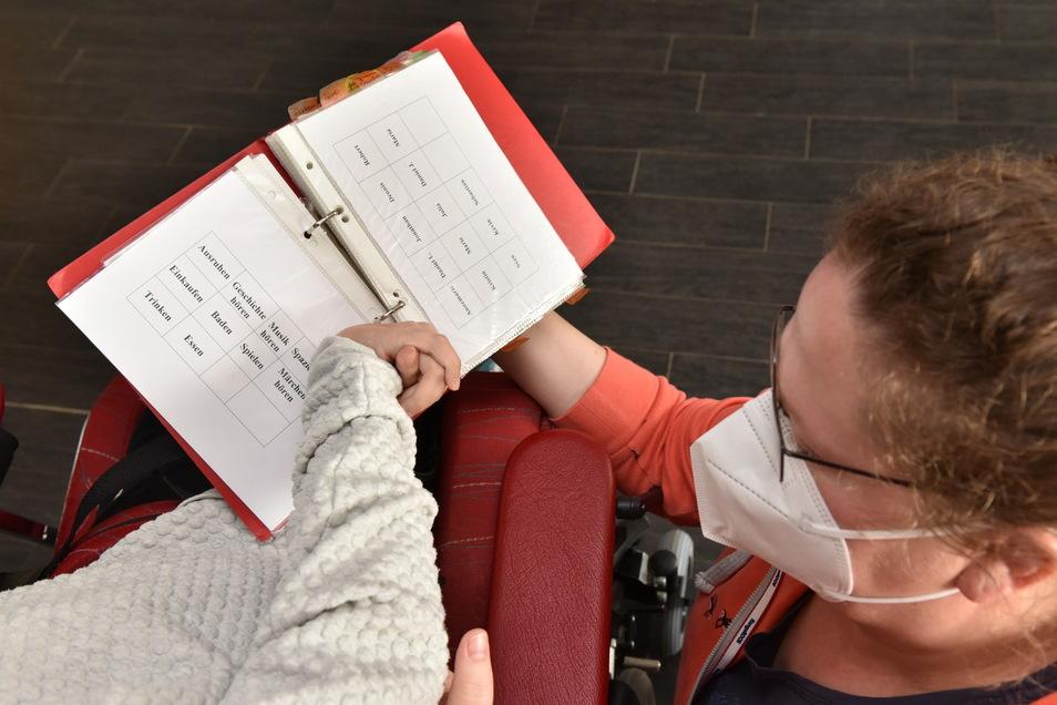 Steffi Haase vom Betreuerteam der Arbeiterwohlfahrt in Reinholdshain hilft Annemarie, sich verständlich zu machen. Das klappt mit Hilfe der eigens zusammengestellten Buchstabenmappe.