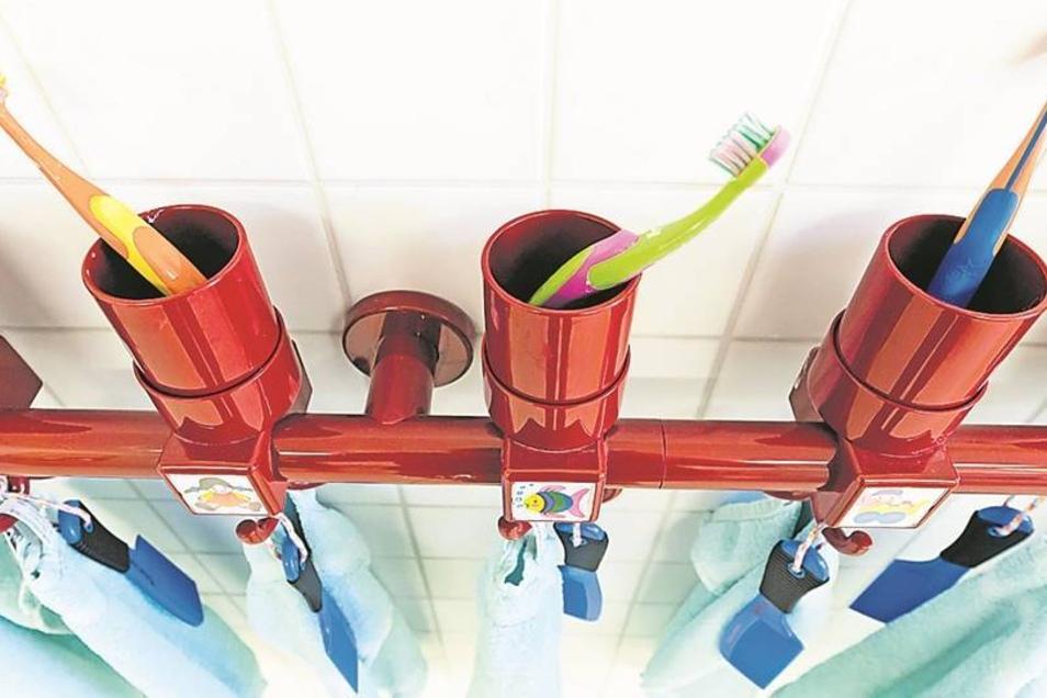 In Reih und Glied stehen die Zahnputzbecher der Kindergartenkinder nebeneinander. Kleine Bilder verraten, welche Zahnbürste zu welchem Kind gehört.