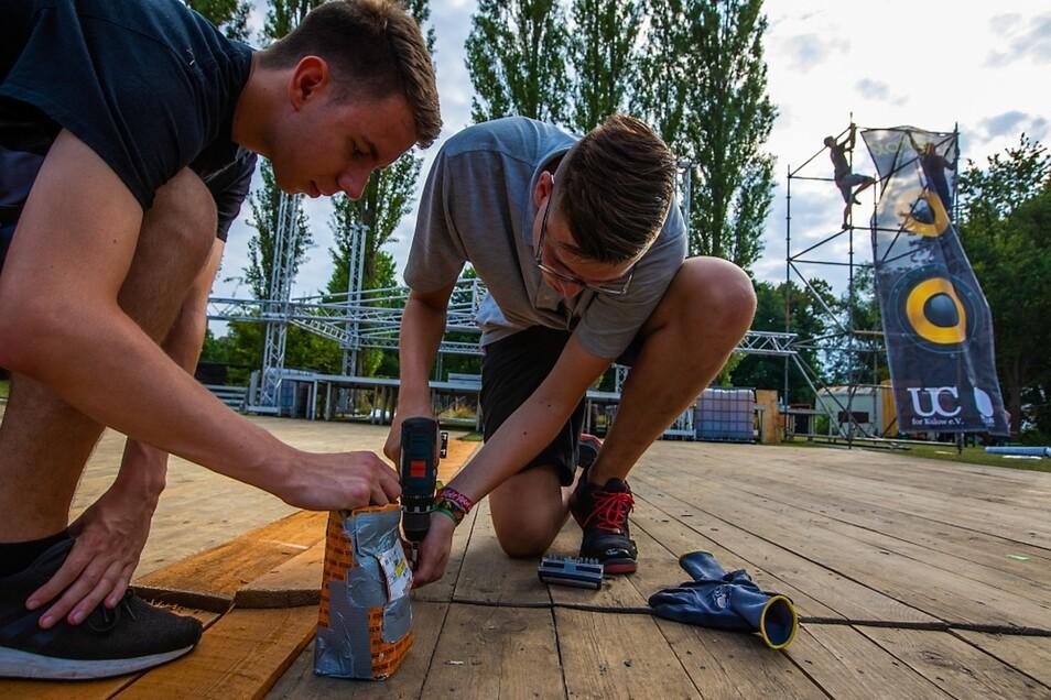 Aufbau der Bühne und Tanzfläche für das 7. Stadtteichfestival in Wittichenau. Philipp und Hubert, beide aus Wittichenau, verschrauben die Bretter der Tanzfläche vor der Bühne.
