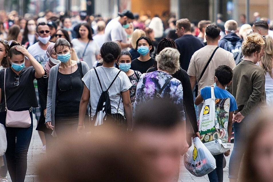 Zahlreiche Menschen mit Masken sind auf der Schildergasse in Köln unterwegs.