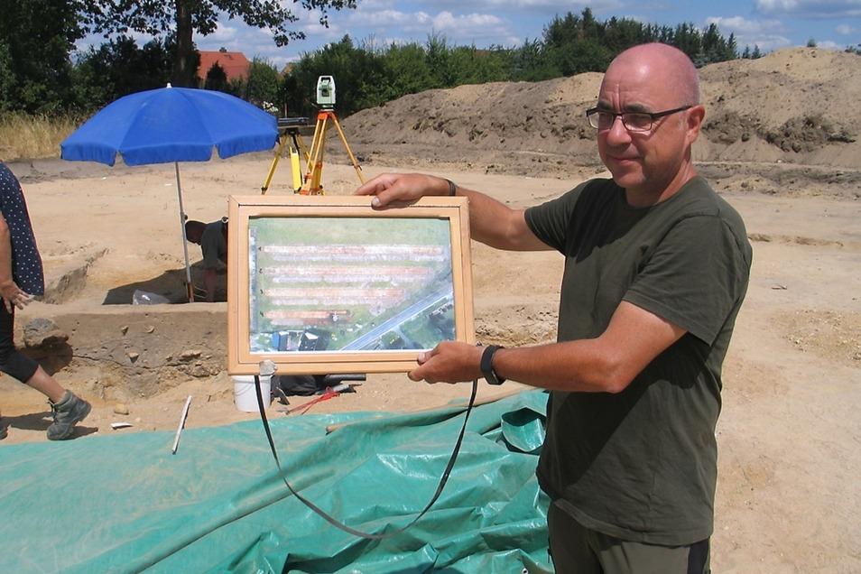 Grabungsleiter Olaf Ullrich zeigt die Drohnenaufnahme mit den Suchstreifen.