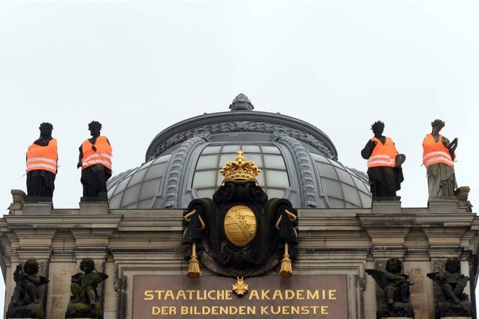 """Am Montag hatten Dresdner Kunststudenten unter anderem an der Staatlichen Akademie der Künste die Figuren auf dem Dach  mit Warnwesten versehen. Weiter unten - nicht im Bild - hing zusätzlich ein Banner mit einem Zitat von Johann Wolfgang von Goethe """"Das Land, das die Fremden nicht beschützt, geht bald unter""""."""