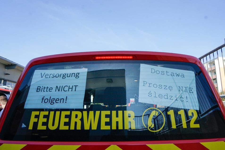 Schilder in deutscher und polnischer Sprache hängen im Heck der Versorgungsfahrzeuge. Sie warnen davor, den Fahrzeugen zu folgen.
