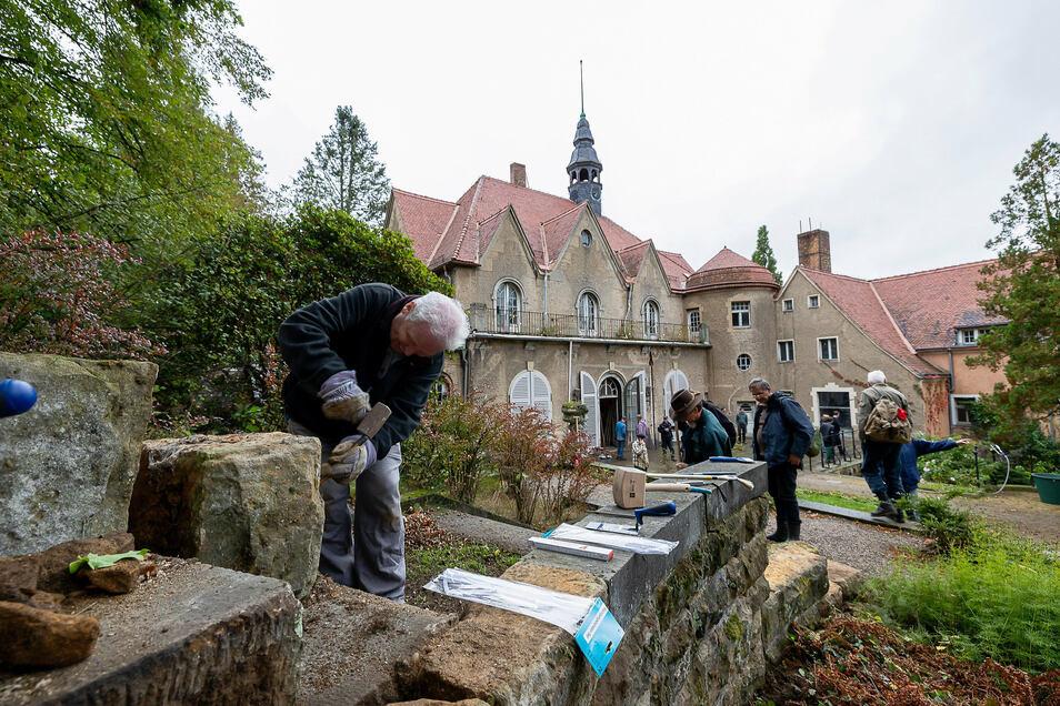 Jürgen Weigelsdorf bearbeitet die Stützsteine einer Treppe im Thürmsdorfer Park, damit sie wieder fest verfugt werden können.
