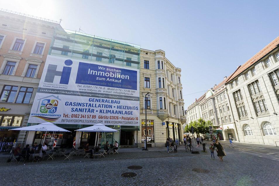 Die Fassade des Hauses Postplatz 16 in Görlitz wird von zwei riesigen Plakaten verdeckt.