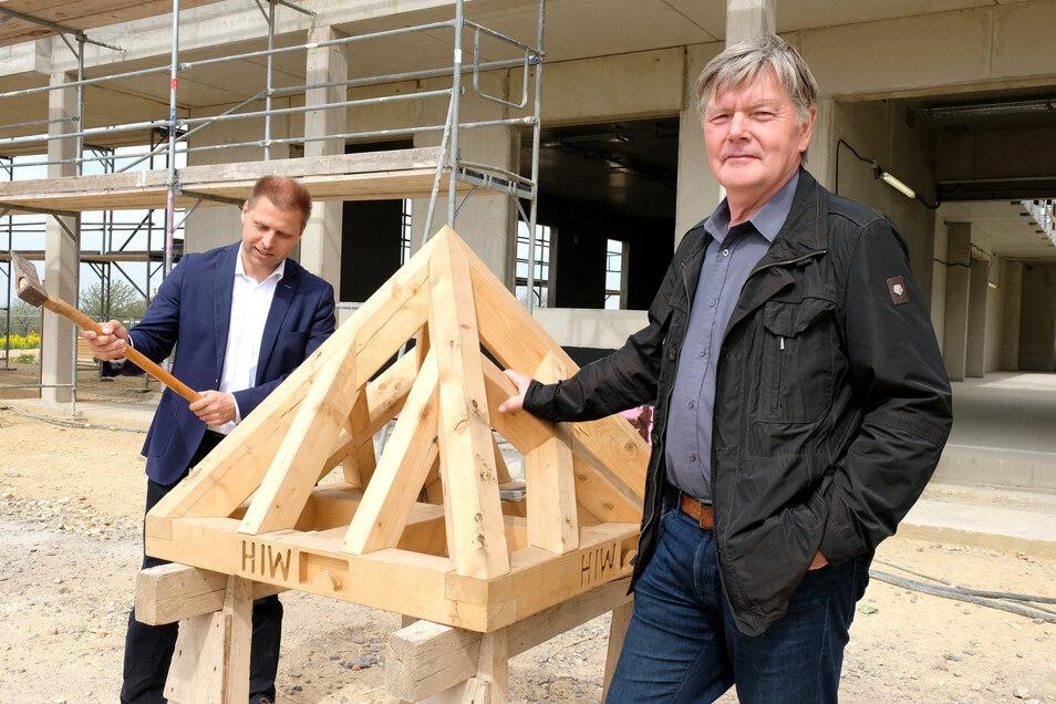 Der Rohbau des neuen Schulgebäudes in Klipphausen ist fertiggestellt. Bürgermeister Mirko Knöfel (links) schlägt gemeinsam mit Alt-Bürgermeister Gerold Mann den letzten Nagel ein.